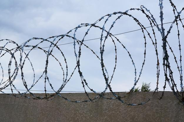 Fil de fer barbelé sur le fond d'une clôture en béton et ciel nuageux.