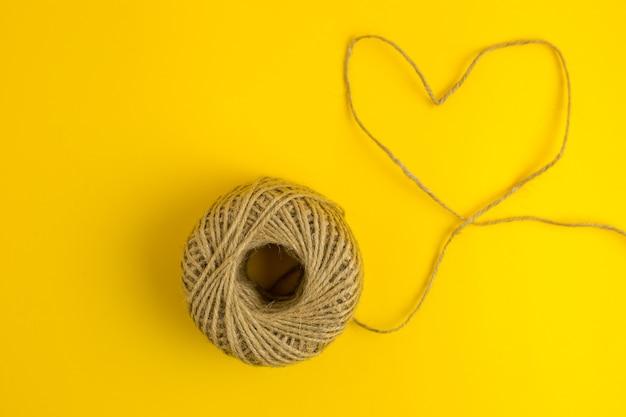 Un fil en forme de coeur sur fond jaune. style plat