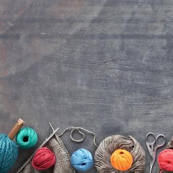 Fil de laine et aiguilles à tricoter, fond de tricot créatif sombre avec espace copie