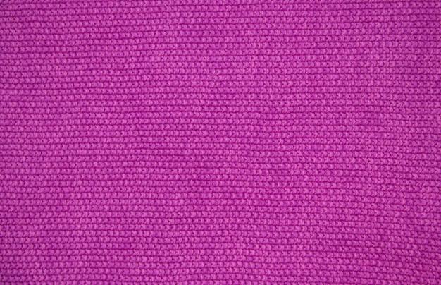 Fil de laine rose de texture tricotée. tricot à la main. fermer. fond rose.