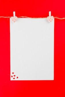 Fil de lin avec une feuille de papier vierge et des coeurs