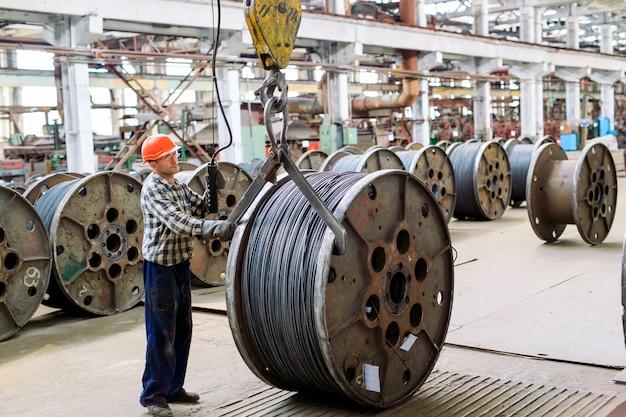 Fil machine, raccords dans les entrepôts. travailleur à côté d'un paquet avec catalkoy. entrepôt industriel à l'usine métallurgique.