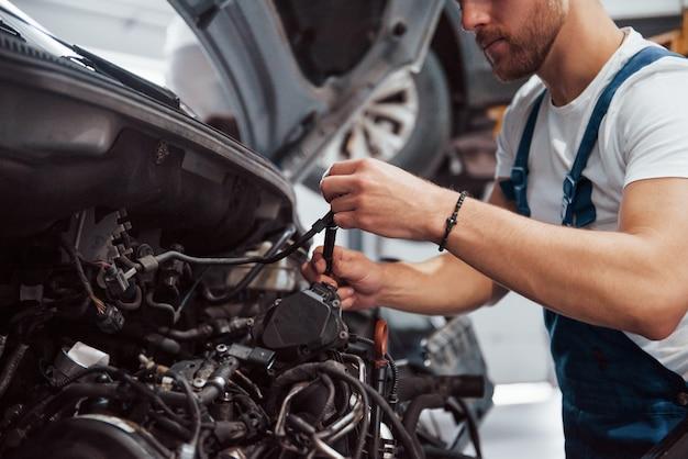 Fil pour embrayage en mains. l'employé en uniforme de couleur bleue travaille dans le salon automobile.