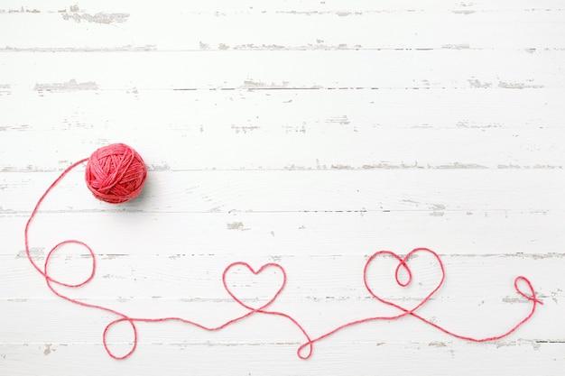 Fil rouge, deux coeurs et enchevêtrement sur bois clair