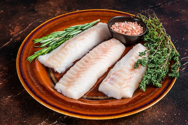 Filet d'aiglefin cru sur une assiette rustique avec du thym et du sel. fond sombre. vue de dessus.