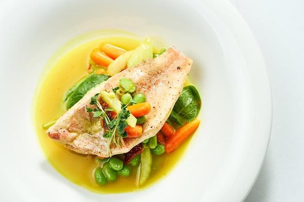 Filet de bar frit avec compote de légumes et sauce à l'orange dans une assiette blanche. isolé sur une surface grise.