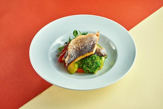 Filet de bar frit avec des légumes cuits à la vapeur pour garnir dans une assiette blanche sur une surface colorée.