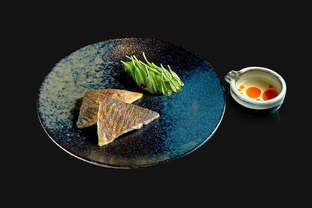 Filet de bar grillé aux épinards et sauce jaune dans une assiette en céramique. livraison de nourriture. isolé sur fond noir