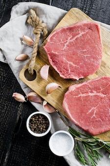 Filet de bifteck de bœuf cru sur une planche à découper en bois, ail et un brin de romarin.