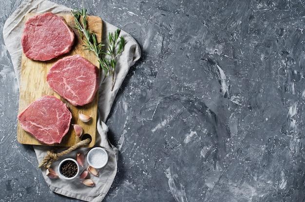 Filet de bifteck sur une planche à découper en bois, ail et un brin de romarin.