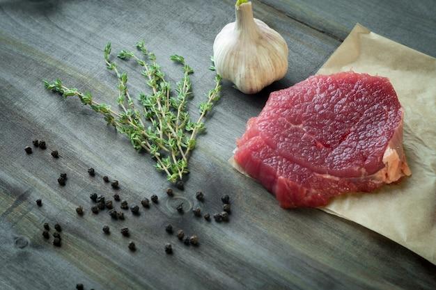 Filet de bœuf cru à l'ail et au thym sur une table en bois foncé