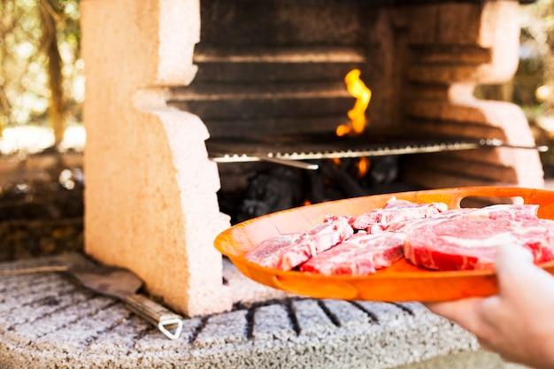 Filet de boeuf cru sur une assiette en plastique pour griller au barbecue