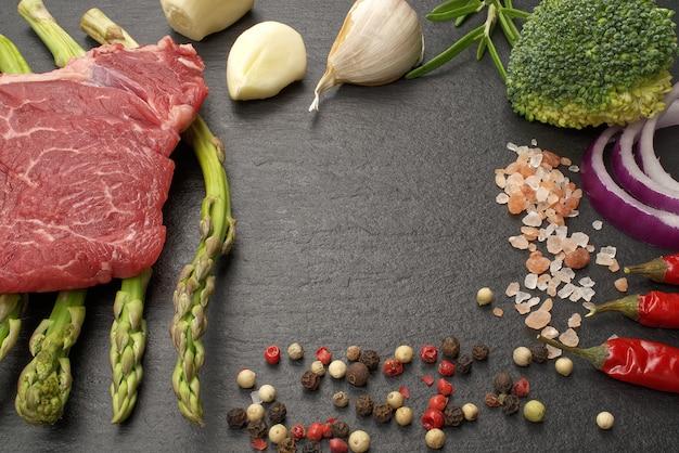 Filet de boeuf cru sur planche de pierre noire avec asperges et épices sèches prêt à cuire