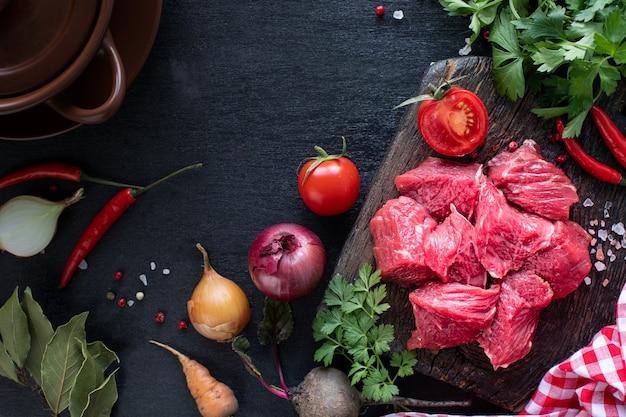 Filet de boeuf cru prêt à griller. filet de veau sur une planche à découper en bois avec tomates cerises, piment et herbes. ingrédients pour soupe ou bortsch. copie espace. vue de dessus.