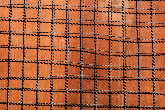 Filet de cage métallique avec ombre sur plaque de bois marron