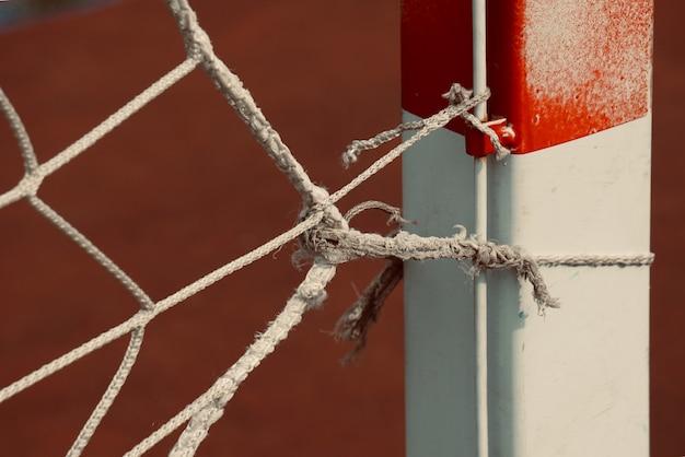 Filet de corde dans le but de football, vieille toile de corde cassée