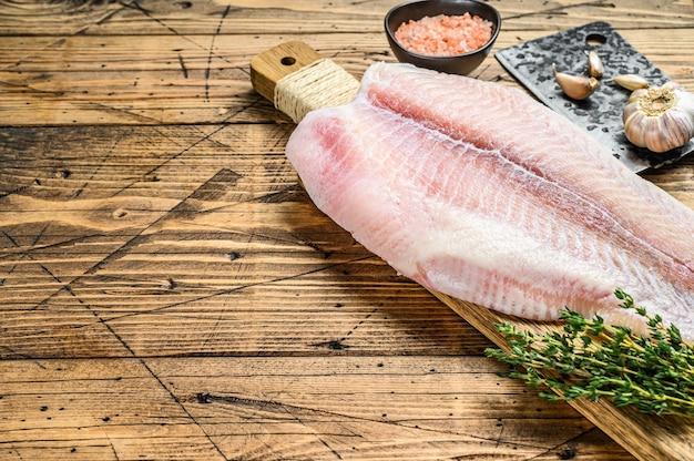 Filet cru de poisson pangasius sur une planche à découper. fond en bois. vue de dessus. copiez l'espace.