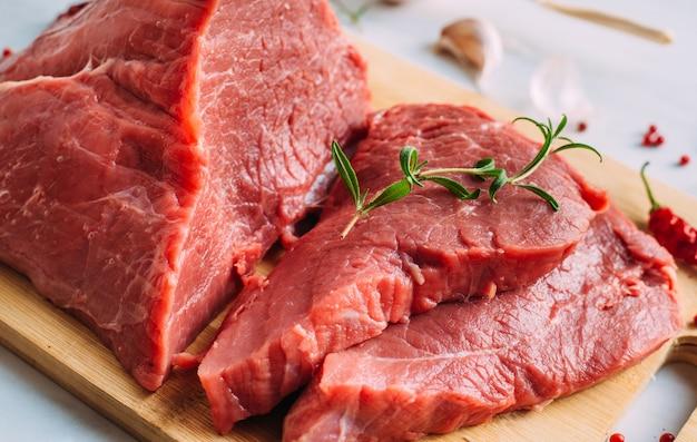 Filet cru de porc frais sur planche de bois. viande de boeuf rouge sur une planche à découper.