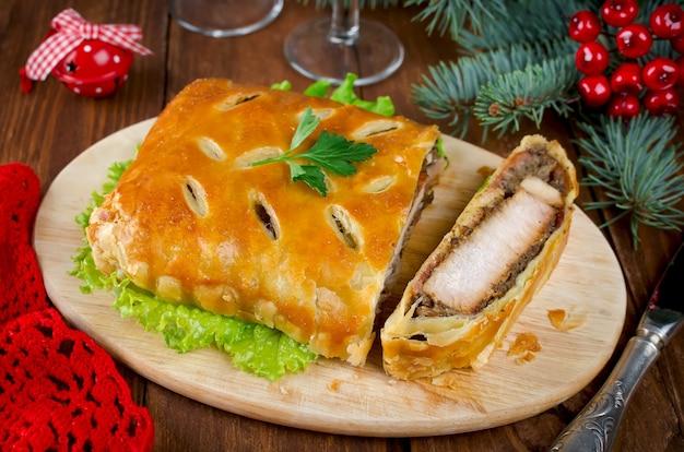 Filet de dinde aux champignons, cuit en pâte feuilletée. couper la viande sur une planche à découper en bois