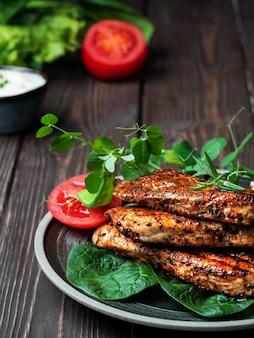 Filet de dinde rôtie avec croûte frite appétissante lumineuse avec des épices et des herbes de printemps sur une plaque noire