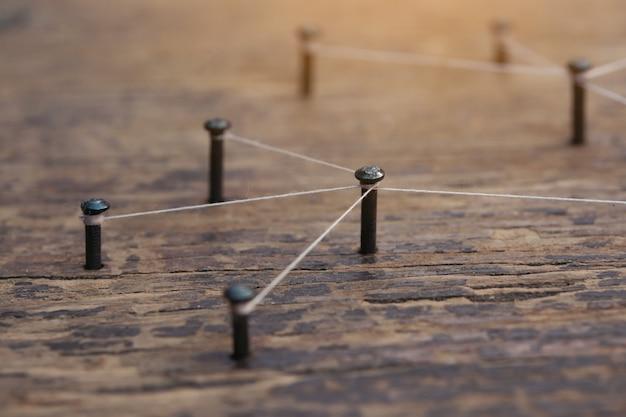 Filet fait par un fil entre les clous sur planche de bois