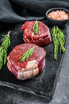 Filet de filet de steak cru sur une planche de pierre. surface noire. vue de dessus.