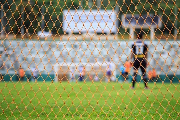 Filet de football orange et flou de joueur dans le stade