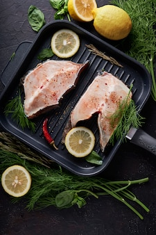 Filet frais de poisson de mer dans une lèchefrite sur fond sombre.