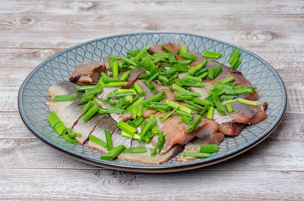Filet de hareng coupé en morceaux avec des oignons verts sur une assiette bleue. fond de bois clair.