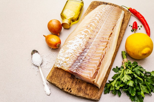 Filet de longe de morue cru aux légumes, épices, huile d'olive et sel.
