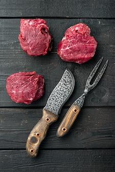 Filet mignon cru ou steaks d'oeil aux herbes et épices, sur table en bois noir