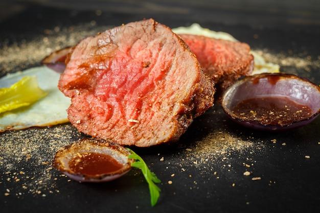 Filet mignon avec sauce rouge et purée de pommes de terre sur une plaque de schiste