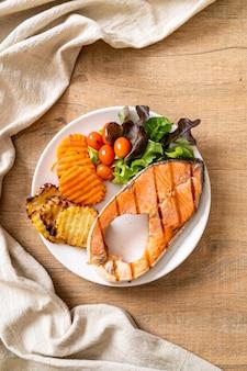 Filet de pavé de saumon grillé aux légumes et frites sur assiette
