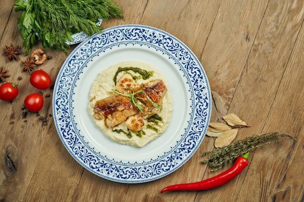 Filet de perche frit avec purée de chou-fleur dans une assiette blanche sur une surface en bois. délicieux fruits de mer avec garniture