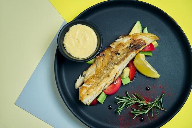 Filet de perche frit avec salade d'avocat, tomate dans une assiette noire sur s. gros plan, vue de dessus