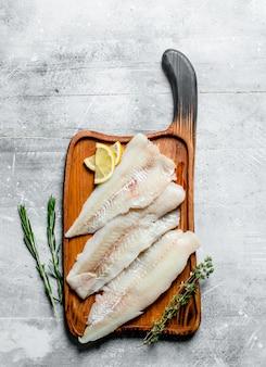 Filet de poisson aux tranches de citron, thym et romarin. sur une surface rustique blanche