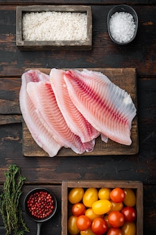 Filet de poisson blanc, avec du riz basmati et des ingrédients de tomates cerises, sur la vieille table en bois, vue du dessus