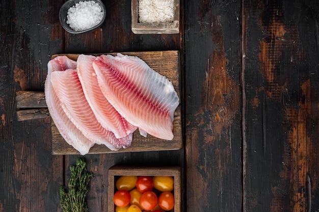 Filet de poisson blanc, avec du riz basmati et des ingrédients de tomates cerises, sur une vieille table en bois