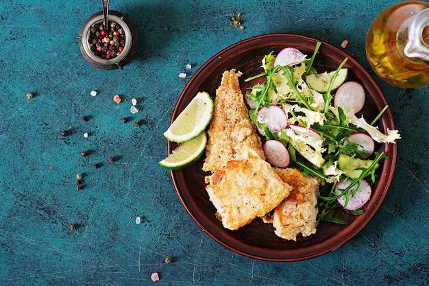 Filet de poisson blanc frit et salade de concombre et radis. vue de dessus