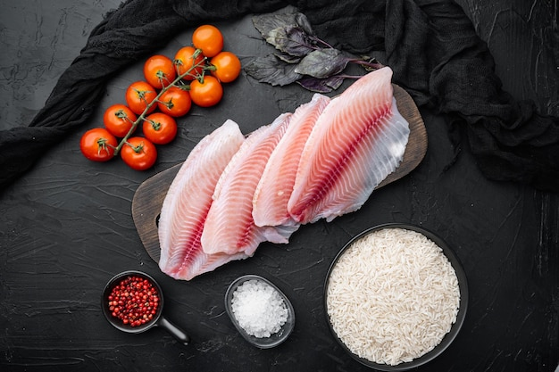 Filet de poisson blanc, avec riz basmati et ingrédients de tomates cerises, sur fond noir, vue de dessus
