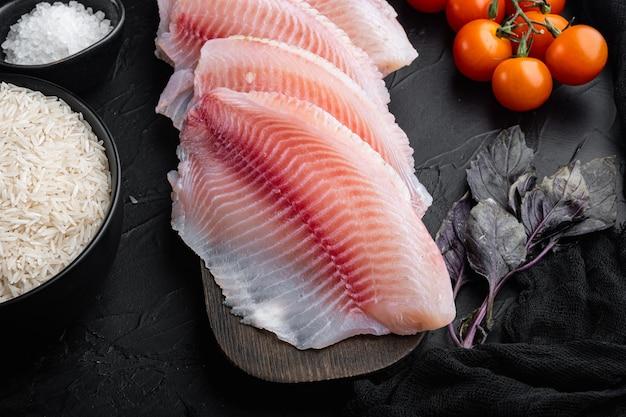 Filet de poisson blanc, avec riz basmati et ingrédients de tomates cerises, sur fond noir