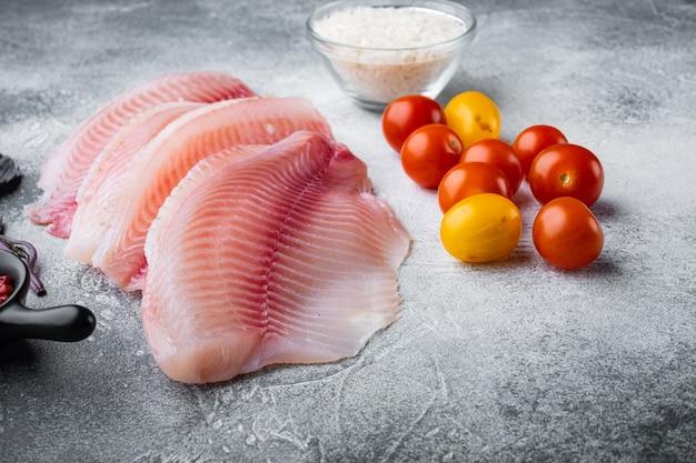 Filet de poisson blanc, avec riz basmati et ingrédients de tomates cerises, sur table grise
