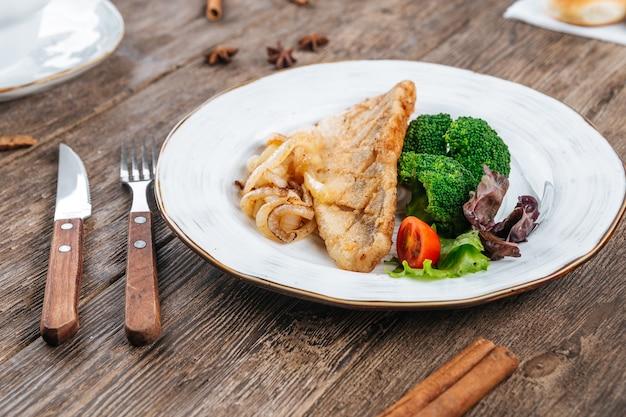 Filet de poisson frit avec des légumes frais sur une table en bois