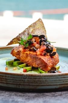 Filet de poisson frit placé sur des tranches d'avocat et une sauce garnie d'olive tomate et de peau de poisson