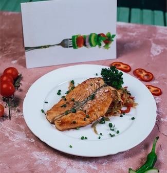 Filet de poisson grillé avec des herbes hachées et des tomates.