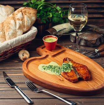 Filet de poisson grillé et servi avec une sauce crémeuse aux herbes et un verre de vin blanc.