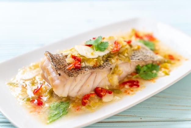 Filet de poisson mérou cuit à la vapeur avec sauce chili et citron vert dans une vinaigrette au citron vert