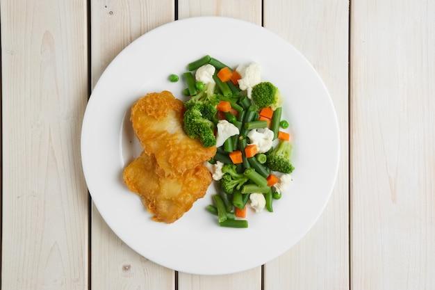 Filet de poisson en pâte avec légumes bouillis