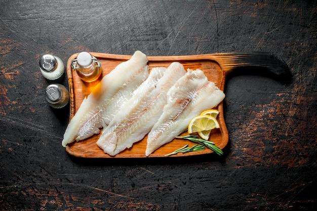 Filet de poisson sur une planche à découper avec des tranches de citron, huile et épices sur table rustique sombre