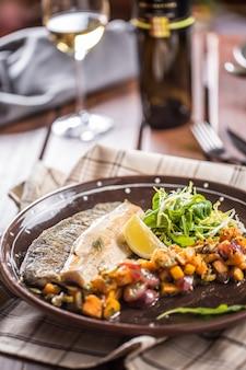 Filet de poisson rôti avec morceaux de citrouille et décoration d'herbes dans un pub ou un restaurant.